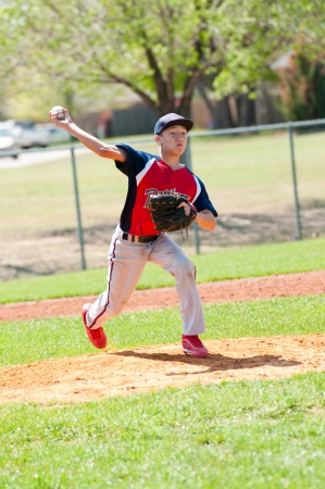 Teen baseball pitcher throwing the pitch photo