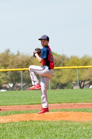 Teen boy baseball pitcher about to throw a pitch. photo