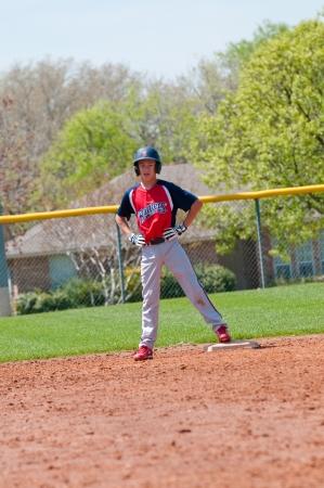 ballplayer: Teen baseball boy standing on second base.