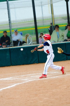 Little league baseball boy swinging the bat and about to hit the ball.