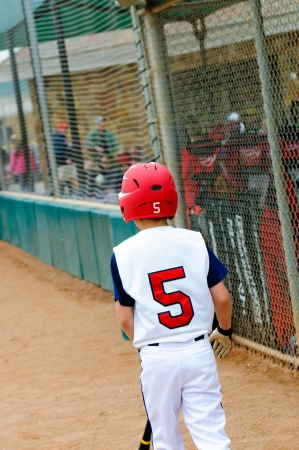 Little league baseball batter walking out to base. photo