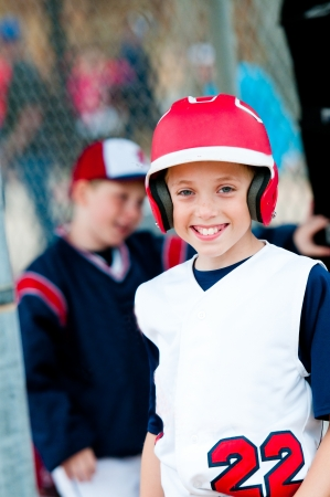 Little league baseball boy with helmet in dugout smiling.