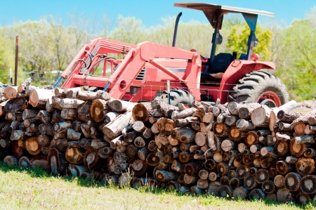 Stack of firewood with tractor in background.