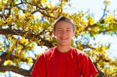 Teenage boy up in the tree happy and smiling. photo