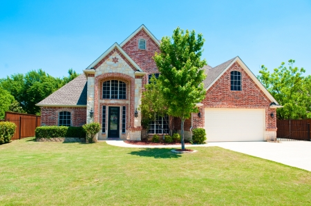single story: Two story brick residential home with the garage in the front.