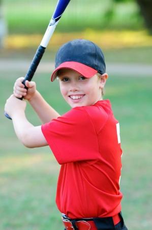 Portrait of little league baseball boy holding bat. Stock Photo