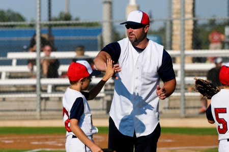Baseball boy giving coach a high five during a game.