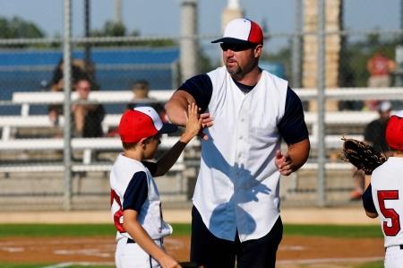 Muchacho del béisbol dando un máximo de cinco entrenador durante un partido.