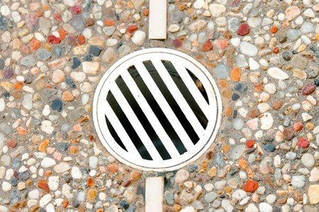 aggregate: Outdoor drain in aggregate decking around a pool.