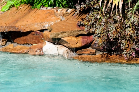 Pool waterfall with lush landscape and aqua blue clear water. photo