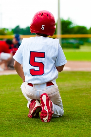 Baseball boy kneeling on the ground while an injured player is on the field. photo