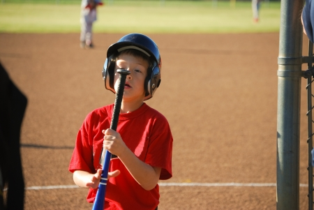 Little league baseball boy staring at end of bat. photo