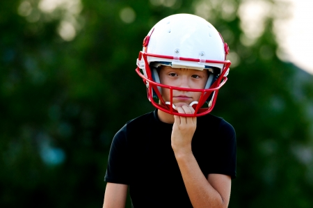 football cleats: Young football boy in helmet with sad look on face.