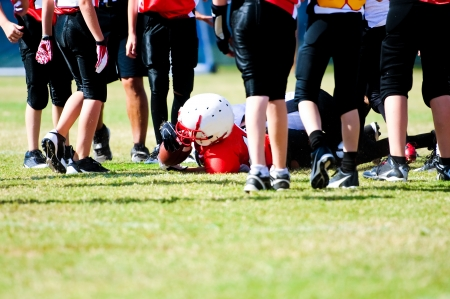 tackle: Tackled football boy in the middle of a group of players. Stock Photo