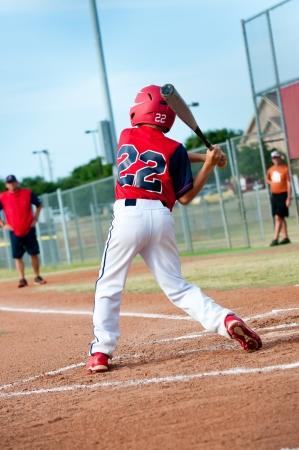 Niño del béisbol joven manejando el bate durante un juego.
