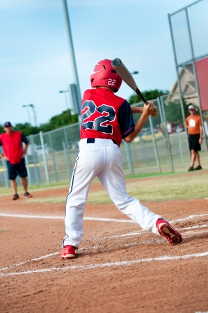 little league: Young baseball kid swinging the bat during a game.