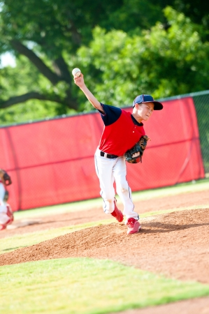 Little league baseball boy pitching during a game.