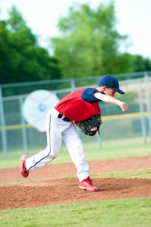 Little league baseball boy pitching during a game. photo