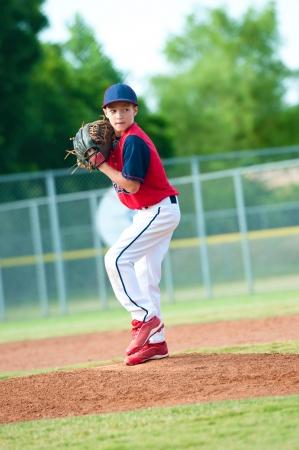 guante de beisbol: Niño pequeño béisbol de la liga de pitcheo durante un juego. Foto de archivo
