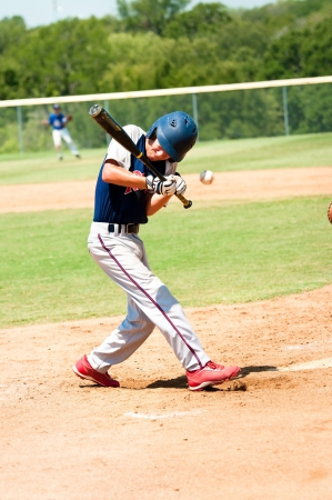 little league: Teen baseball player getting hit by baseball during a game.