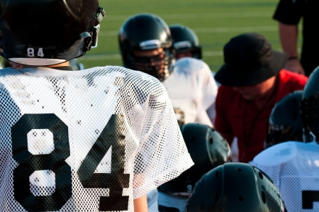 Young american football team in a huddle with the coach. Stock Photo