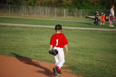 Little league youth baseball player walking on field. Stock Photo