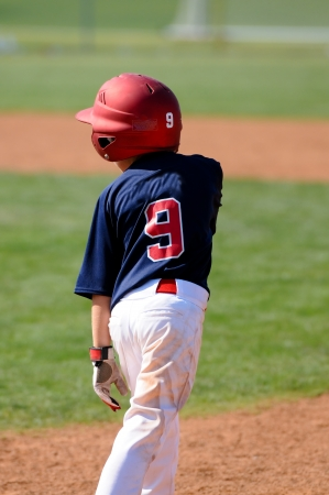 Little league baseball boy standing on base with helmet photo