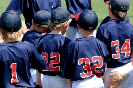 Team of baseball boys during a game in a huddle.