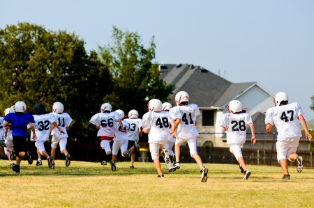 Teen football team running during practice