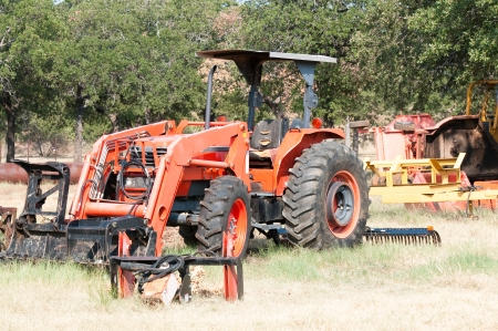 Old orange tractor and equipment on a farm