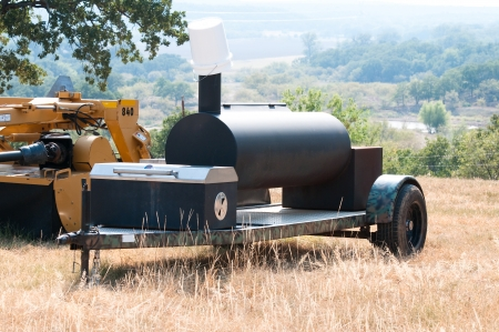 Smoker grill on a camo trailer out on a farm with a scenic view in background