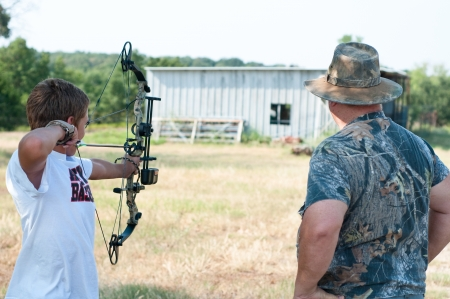 Teenage boy shooting his bow with grandpa on a farm.