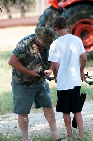 Teenage boy getting help with his bow from grandpa. photo
