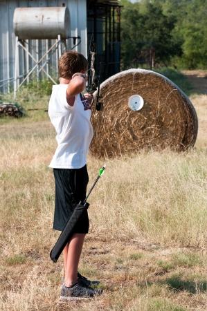 Cute teenage boy shooting a boy outdoors on a farm. Фото со стока