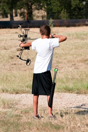 Cute teenage boy shooting a boy outdoors on a farm. photo