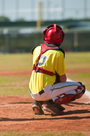 Baseball player as catcher wearing yellow uniform during a game. photo