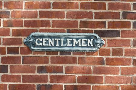 urban area: Old vintage gentlemen restroom sign on red brock wall in urban area.