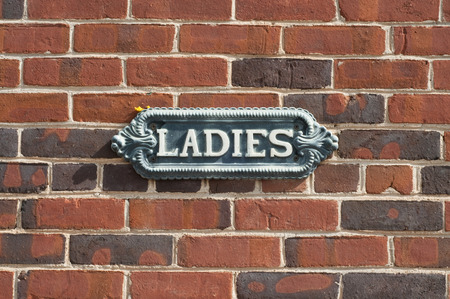 old antique ladies restroom sign on red brick wall stock photo