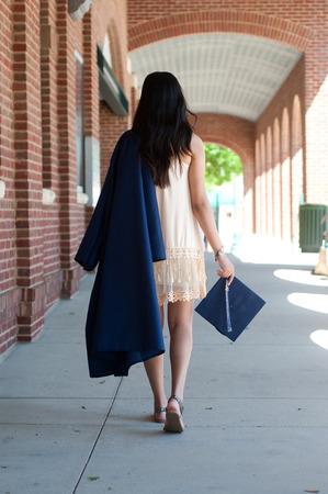 Teen graduate girl walking away from camera wearing robe. Фото со стока