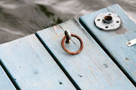 wooden dock: Close-up of an old blue wooden dock on a lake.