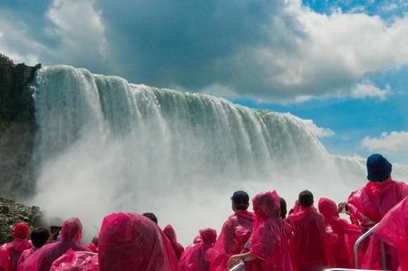 Tourist in rain coats looking up at Niagara Falls, Ontario, Canada