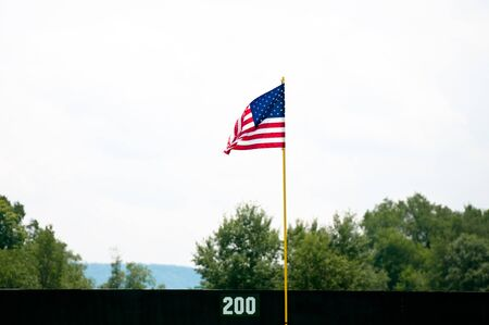 outfield: An American flag hung in the outfield of a baseball field Stock Photo