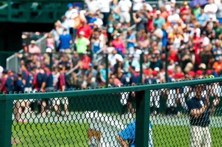 yahoo: Crowd of fans blurred out with closeup of green fence during a game Stock Photo