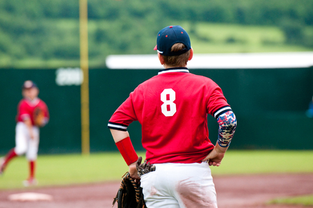 Youth baseball player on third base with hands on hips. Stock Photo