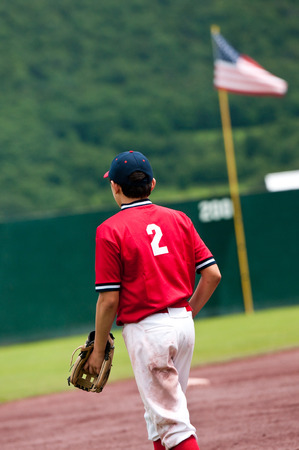 outfield: Youth baseball teen walking with American flag in the outfield. Stock Photo