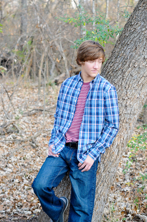 Knappe tiener leunend op boom op zoek triest.
