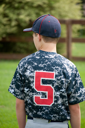 little league: Little league baseball player with camo jersey from behind. Stock Photo