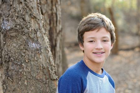 Jonge knappe jongen met beugels, glimlachend naast boom Stockfoto