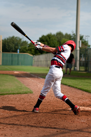 Little league baseball player at the plate, swinging the baseball bat from behind. Stock Photo