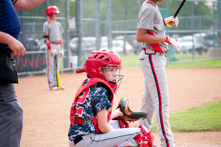 Young baseball boy catcher getting signals from coach with referee. Stock Photo